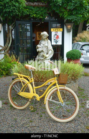 Yellow Nel Lusso Huffy bicycle parked in front of an art gallery in Kennebunkport, Maine, USA. - Stock Image