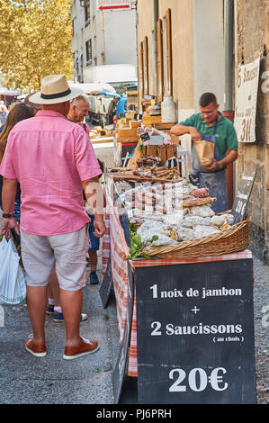 Market trader selling meats during the market at Lamastre, Ardeche, Rhone Alps, France - Stock Image