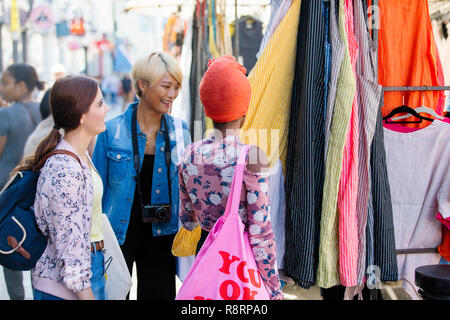 Young women friends shopping on urban sidewalk - Stock Image
