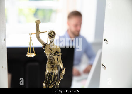 Justice Statue On Shelf And Lawyer Working In Office At background - Stock Image