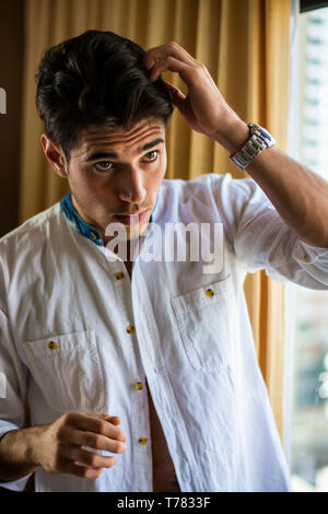 Sexy handsome young man standing and dressing, in his bedroom next to window curtains - Stock Image
