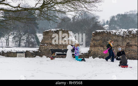 People making a snowman in Verulam Park, St. Albans, Hertfordshire UK - Stock Image