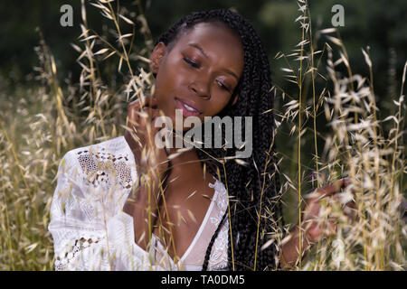 Beautiful young black woman enjoying nature in a high grass meadow - Stock Image