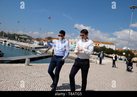 Young businessmen walking talking in conversation on the Doca de Belem marina at lunchtime in  Belem Lisboa Lisbon Portugal Europe EU  KATHY DEWITT - Stock Image