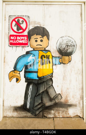 'No Boys Allowed' Graffiti by James Ame - Ame72 (The `Lego Guy)  -  on the exterior of the leisure centre in Aberystwyth, showing an unhappy boy in a GK  netball vest, in reference to the ban by the Urdd ( a welsh langiage youth organisation) on boys competing in netball competitions.  March 10 2019 - Stock Image