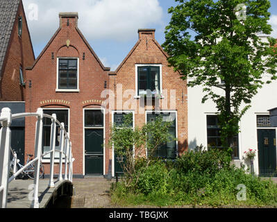 Delft, Netherlands - May 31 2019: Typical Dutch old canal houses in Delft and beautiful small white bridge on the Geerweg - Stock Image