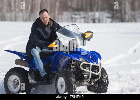 A winter forest. Cold weather. A man riding a big snowmobile - Stock Image