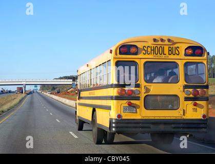 Yellow School bus transporting children to school. - Stock Image