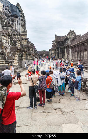 Angkor Wat, Cambodia - 11th January 2018: Chinese tourists pose for photos, Huge numbers visit the temple complex - Stock Image