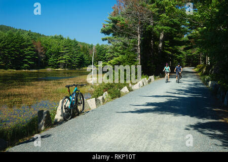 Couple riding their bicycles on the Eagle Lake loop carriage road, Acadia National Park, Maine, USA. - Stock Image