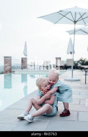 Sisters hugging at swimming-pool - Stock Image