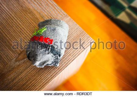 Poznan, Poland - November 8, 2018: Gray child socks laying on a wooden table corner. - Stock Image