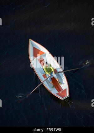 An elderly man rowing alone a small fiberglass rowboat , Finland - Stock Image