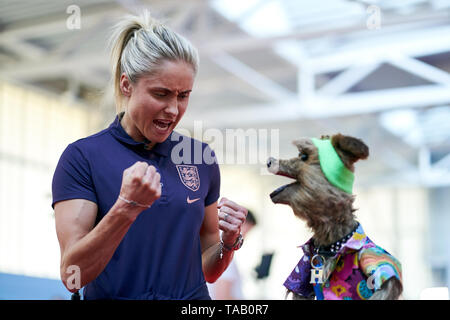England women's captain Steph Houghton shows Hacker T. Dog how to celebrate a goal during the media day at St George's Park, Burton. - Stock Image