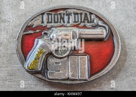 Close-up of a belt buckle with a smoking revolving on it and the text 'I don't dial 911', concrete background - Stock Image