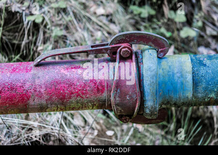 Coupling of red and blue pipe close-up. Old colored metal piping with clutch with blurred green grass in background. Cohesiveness and fixed connection. - Stock Image