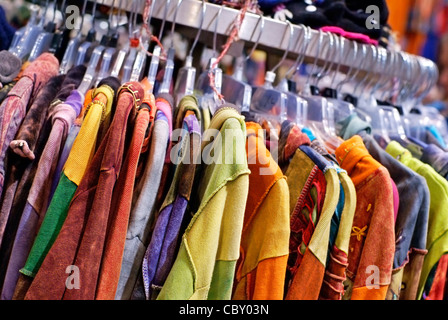 Colorful clothes hanging on a clothes rack in a retail store. - Stock Image