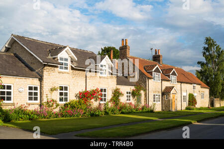 A row of stone built houses and cottages along Railway Street in Slingsby, North Yorkshire, England, UK - Stock Image