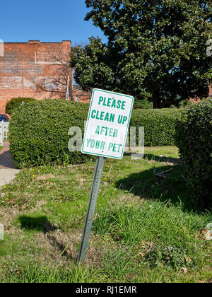 Please clean up after your pet warning sign or caution sign in a grassy urban area in Montgomery Alabama, USA. - Stock Image