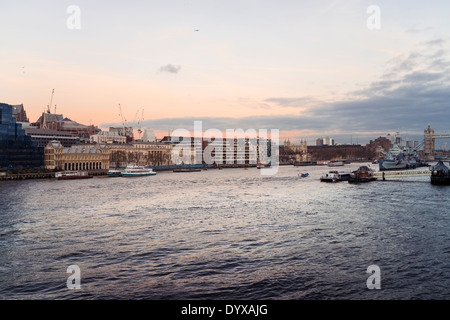 Cityscape of the city of London looking at a sunset over the river Thames with part of Tower Bridge and the Tower of London. - Stock Image
