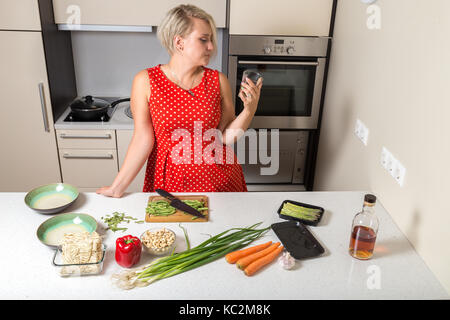 Young girl looking at whiskey glass in hand - Stock Image
