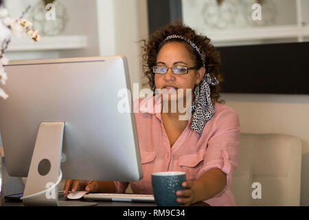 Happy woman working from her home office. - Stock Image