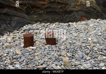 Two old push boat mooring cleats used as fishermen stools by the beach amongst stones and peebles. - Stock Image