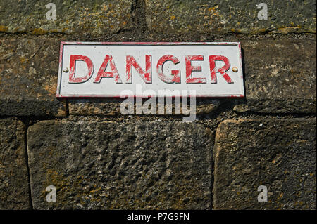 Metal plaque with the word DANGER on a stone wall - Stock Image
