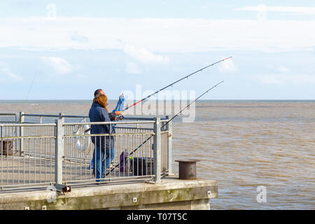 Southwold, UK - September 10, 18 - People fishing with fishing rods on Southwold Pier - Stock Image