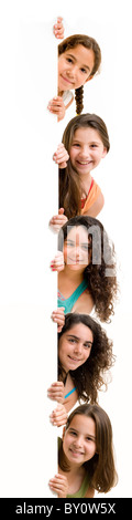 five girls peeking behind a white wall or sign isolated on white. - Stock Image