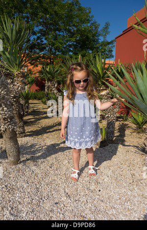 Young girl playing in amongst a maze of small palm trees. - Stock Image
