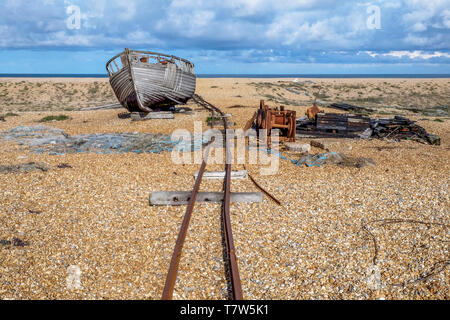 Old rusty train track on a big flat pebble beach leading to an old wooden fishing boat that is sitting on the beach, scattered across the beach are ol - Stock Image