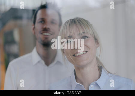 Successful businesswoman and businessman looking out of window, smiling - Stock Image