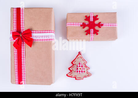Wrapped vintage gift boxes with red ribbon bow and Christmas ornaments - Stock Image