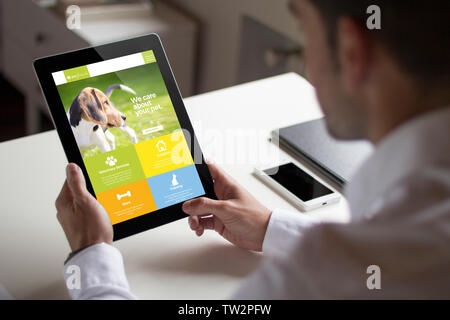 bussinessman at office holding a tablet showing pet website. All screen graphics are made up. - Stock Image