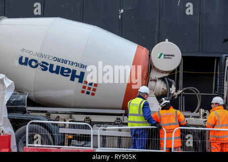 Construction workers in hard hats and yellow and orange jackets look on at a cement truck marked Hanson on a building site in central London, UK - Stock Image