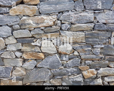 Granite wall made of stacked pieces stones. Full frame image as background. - Stock Image