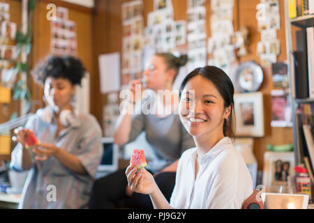Portrait smiling creative businesswoman eating watermelon in office - Stock Image