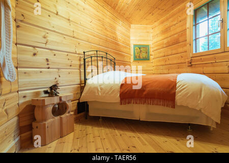 Queen size bed with antique metal headboard, white bedspread and red throw in irregular shaped bedroom inside a piece sur piece Scots pine log home, Quebec, Canada. This image is property released. CUPR0334 - Stock Image