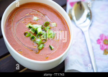 Traditional spanish vegan gazpacho presented on a wooden table with olive oil and fresh chopped cucumber and scallion - Stock Image