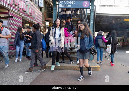 Teenage students returning from school and others emerge from the 7 train on 82nd Street in Jackson Heights, Queens, New York City - Stock Image