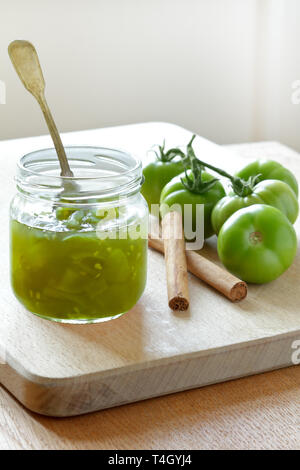 Green tomato jam or chutney in a glass jar with cinnamon flavoring, home canning concept - Stock Image