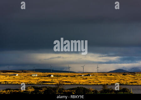 Maas, County Donegal, Ireland. 11th January 2019. The rising sun illuminates coastal cottages and a windfarm as stormclouds move across the landscape on the north-west coast. Credit: Richard Wayman/Alamy Live News - Stock Image