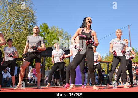 Nis, Serbia - April 20, 2019 Group of people practicing Piloxing sport in an outdoor class in summer with instructor - Stock Image