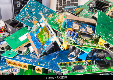 E-waste heap from old discarded laptop and PC parts. Industrial background from electronic components. Mainboards, PCB, cards and keyboards. Ecology. - Stock Image