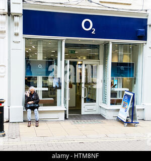 Lady on mobile phone outside o2 phone shop on high street UK England talking on mobile phone sat on store window - Stock Image