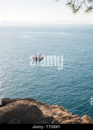 Small fishing boat close to the rocky coast and pine trees in Croatia - Stock Image