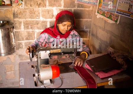A woman making clothes using an old-fashioned sewing machine. Kakani village, Jodhpur, Rajasthan, India. - Stock Image