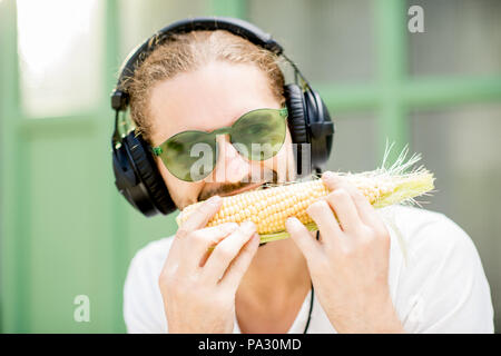 Funny musician playing harmonica with corn outdoors on the green background - Stock Image