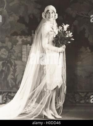 Bride carrying bouquet of lilies - Stock Image